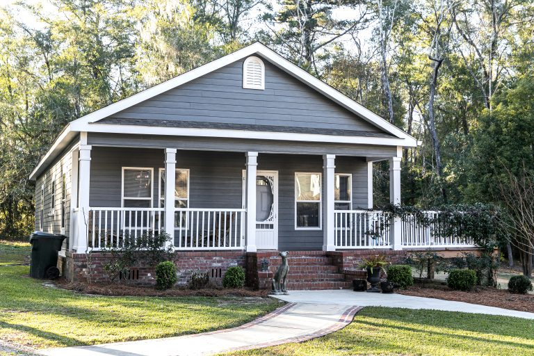 Small blue gray mobile home with a front and side porch with white railing - 365 RPM