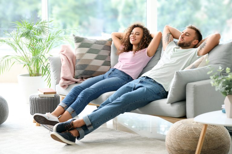Greeley Happy young couple relaxing on sofa at home